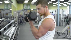 Portret van de sterke atletische mens bij de gymnastiek opleiding de bodybuilder doet een oefening op de bicepsen met domoren Royalty-vrije Stock Foto