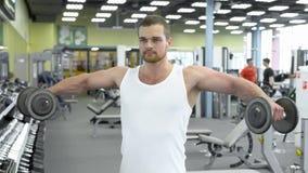 Portret van de sterke atletische mens bij de gymnastiek opleiding de bodybuilder doet een oefening voor schouders met domoren Royalty-vrije Stock Fotografie