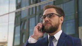 Portret van de stevige jonge mens die op telefoon spreken die zich bij de moderne bouw bevinden backgroung stock videobeelden