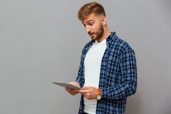 Portret van de verbaasde toevallige mens die tabletcomputer met behulp van Royalty-vrije Stock Afbeeldingen