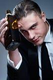 Portret van de vermoeide gedronken mens met whiskyfles royalty-vrije stock afbeeldingen
