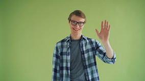 Portret van de vriendschappelijke golvende hand die van de persoonskerel camera en het glimlachen bekijken stock footage