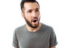 Portret van de vrolijke en zeer verraste mens met baard, in grijs stock foto's