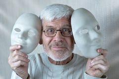 Portret van de vrolijke grijs-haired mens met twee theatrale maskers stock foto's