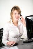 Portret van de vrolijke jonge exploitant van de vrouwentelefoon bij bureau in bureau Stock Afbeeldingen