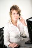 Portret van de vrolijke jonge exploitant van de vrouwentelefoon bij bureau in bureau Royalty-vrije Stock Afbeeldingen