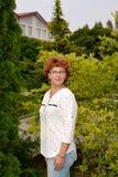 Portret van de vrolijke vrouw van gemiddelde jaren tegen de achtergrond van bomen Stock Foto's