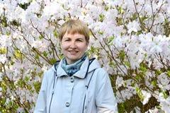 Portret van de vrouw van gemiddelde jaren tegen de achtergrond van de tot bloei komende rododendron van Shlippenbakh royalty-vrije stock afbeeldingen