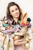 Portret van de vrouw met overvloed van schoenen Royalty-vrije Stock Afbeeldingen