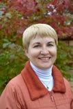 Portret van de vrouw van gemiddelde jaren tegen de achtergrond van een de herfstboom stock fotografie