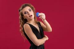 Portret van de vrouwelijke gokker bij het casino die pookspaanders in de hand houden stock foto