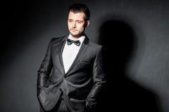 Portret van de zekere knappe mens in zwart kostuum met bowtie Royalty-vrije Stock Fotografie