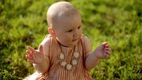 Portret van de zitting van het babymeisje op het gras stock video