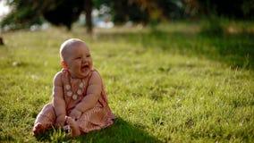 Portret van de zitting van het babymeisje op het gras stock footage