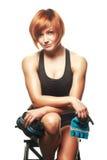 Portret van de zitting van de roodharigevrouw en holdingsriemen en training Stock Fotografie
