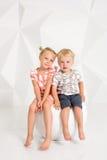 Portret van de zuster en zijn kleine broer bij witte studio Stock Foto