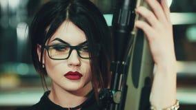 Portret van donkerbruin meisje in glazen en rode lippen Zij houdt sluipschuttergeweer in zijn handen stock videobeelden