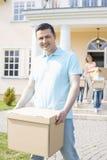 Portret van doos van het mensen de dragende karton terwijl het bewegen van huis met familie op achtergrond stock afbeeldingen