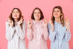 Portret van drie blije jonge meisjesjaren '20 die kleurrijke streep dragen Royalty-vrije Stock Fotografie