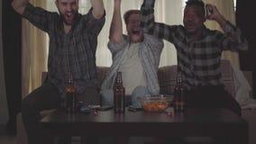 Portret van drie jonge mensenvrienden die bij huis op cauch zitten, kijkend TV, het drinken bier met spaanders, het letten op stock footage