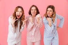 Portret van drie jonge vrouwenjaren '20 die vrije tijds gestreepte clothi dragen Stock Foto