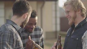 Portret van drie Kaukasische en Afrikaanse Amerikaanse mensen die zich voor groot huis het drinken bier bevinden Één kerel beë stock footage