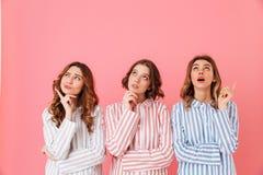 Portret van drie leuke jonge meisjesjaren '20 die kleurrijke gestreept dragen Stock Foto's