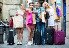 Portret van drie meisjes en de één mens die zich met het winkelen zak bevinden stock fotografie