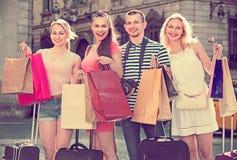 Portret van drie meisjes en de één mens die zich met het winkelen zak bevinden royalty-vrije stock fotografie