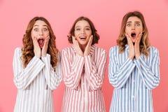Portret van drie opgewekte vrouwenjaren '20 die kleurrijke gestreepte paj dragen Stock Fotografie
