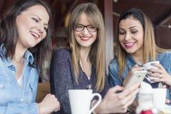 Portret van drie volwassen glimlachende meisjes die een mobiele telefoon met behulp van stock afbeelding