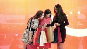 Portret van drie vrij vrouwelijke vrienden die vele het winkelen zakken houden stock footage