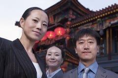 Portret van drie zakenlui met Chinese architectuur op achtergrond. royalty-vrije stock fotografie