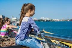 Portret van een 10 éénjarigenmeisje in een profiel Achtergrond van een rivier in een moderne stad, blauwe hemel Royalty-vrije Stock Afbeelding