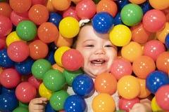 Portret van een aanbiddelijke zuigeling op kleurrijke ballen stock afbeeldingen