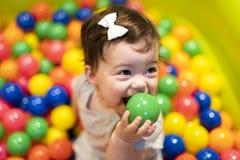 Portret van een aanbiddelijke zuigeling op kleurrijke ballen stock foto's