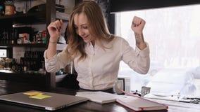 Portret van een aantrekkelijk blondemeisje in een wit zakelijk overhemd zij zorgvuldig de werken een idee komt aan stock videobeelden