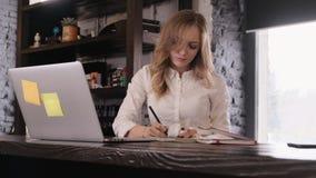 Portret van een aantrekkelijk blondemeisje in een wit zakelijk overhemd zij zorgvuldig de werken een idee komt aan stock video