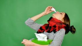 Portret van een aantrekkelijk brunette met griep Het meisje heeft een koude, koorts, is de hals verpakt in een sjaal Zij graaft n stock video
