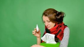 Portret van een aantrekkelijk brunette met griep Het meisje heeft een koude, koorts, is de hals verpakt in een sjaal Zij graaft n stock videobeelden
