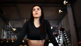Portret van een aantrekkelijk donkerbruin meisje die spleten in de gymnastiek doen stock footage