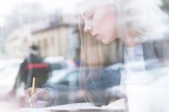 Portret van een aantrekkelijk jong journalistmeisje met pen en blocnote in koffie achter de showcase Niet-contrastmening stock afbeelding