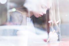 Portret van een aantrekkelijk jong journalistmeisje met pen en blocnote in koffie achter de showcase Niet-contrastmening royalty-vrije stock fotografie