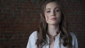 Portret van een aantrekkelijk meisje in een wit blouseclose-up mooi blauw-eyed model die de camera onderzoeken stock video