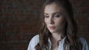 Portret van een aantrekkelijk meisje in een wit blouseclose-up mooi blauw-eyed model die de camera onderzoeken stock footage