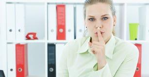 Portret van een aantrekkelijke bedrijfsvrouw met vinger op lippen Jonge onderneemster die in bureau om stilte vragen royalty-vrije stock afbeeldingen