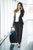 Portret van een aantrekkelijke jonge bedrijfsvrouw die met bagage lopen alvorens op vliegtuig in te schepen royalty-vrije stock afbeelding