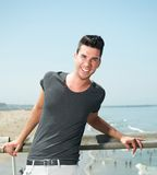 Portret van een aantrekkelijke jonge mens die bij de kust glimlachen Stock Fotografie