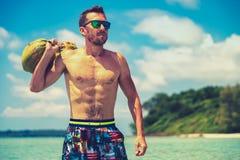 Portret van een aantrekkelijke jonge mens op een tropisch strand stock afbeeldingen