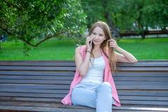 Portret van een aantrekkelijke jonge professionele vrouw die een smartphone gebruiken terwijl het zitten op een houten bank in ee Stock Foto